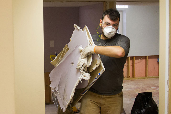 Jim, a volunteer with Nechama, removes drywall from a damaged house in Oak Park.