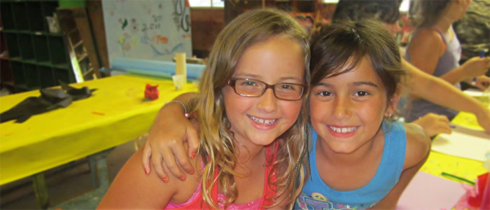 Two campers creating a friendship in crafts class