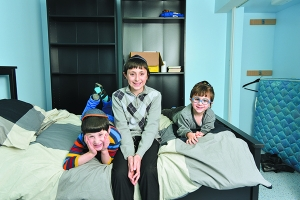 Menashe, Yehuda and Sruli Goldstein of Oak Park relax in one of the renovated bedrooms in their family's basement, which had been badly damaged by flood waters. Photo Credit: Aaron Geler
