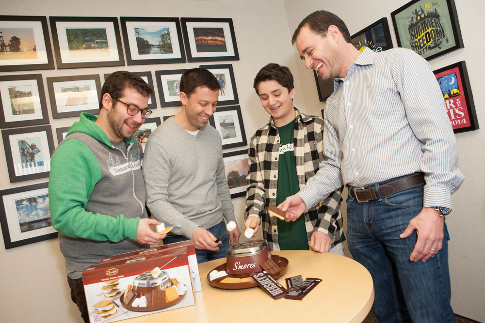 Caption for the group shot: Breaking out a closely-guarded stash of Hershey's chocolate in the Tamarack Camps office in the Max M. Fisher Federation Building Ryan Findling demos the Nostalgic Electric s'more maker for taste-testers, Gabe Neistein, Jason Charnas and Lee Trepeck.